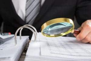 Picture of Man Auditor workers comp Audit Bills Using Magnifying Glass