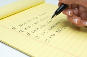 Woman Hand Writing Work Comp Claims Productivity List Of Task To Do