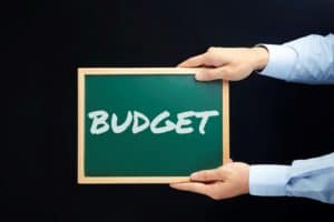 Hands Holding Black Board Cutting Workers Comp Costs With Text Budget