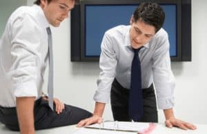 Two Businessman Looking In File Folder Mandolodis Decision Making