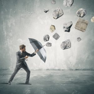 Picture of man using umbrella to protect himself from stone Workers Comp Crisis