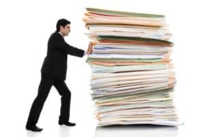 Picture of Man Worker Pushing The Judicial System Giant Stack Documents