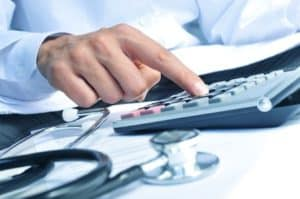 Picture of Man Calculating bill with Stethoscope on the table Bill File Review Workers Comp claims adjuster