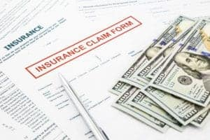 Picture of insurance claim form and money Misconceptions Part II of Workers Comp