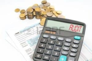 Picture Calculation Workers Comp Premiums Payroll Audit Date with coins and form