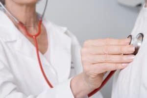 Doctor Medical Practitioner Examines Man Workers Compensation Program With Stethoscope
