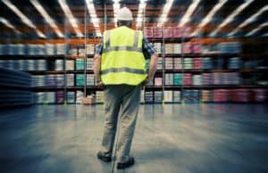 Man Looking at Warehouse Premium Audits Blurry Background