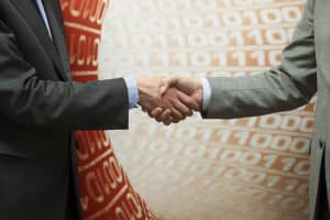 Two businessman changes of company ownership shake hands