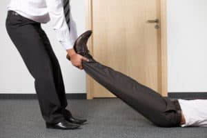 Picture Businessmen Pulling Colleague's Leg at Office Death of Workers Comp Prepare Just In Case