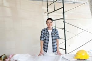 Picture Happy Mid Adult Woman with Building Solid Subcontractor Rules at Construction Site