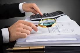 Picture of Auditor Hand Audit Workpapers Using Magnifying Glass And Calculator