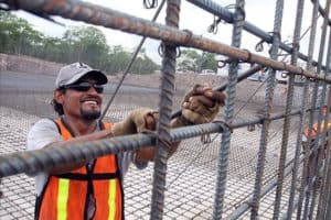 Workers assembling rebar Sliding Scale Dividend Plans for water plan