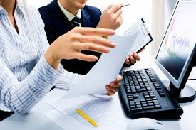 Picture of Two Employer Doing Declarations Page In Front Of Computer
