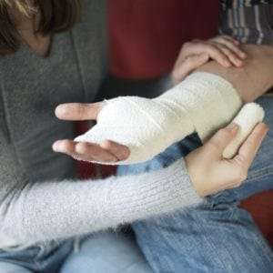 Picture Of Woman Wrapping Temporary Total Disability Man Injured Hand