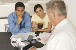 Picture Of Couple Talking To Businessman Workers Comp Premiums Assisting