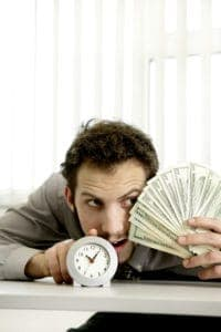 Picture Of Man Holding Money Year End Strategies And Clock
