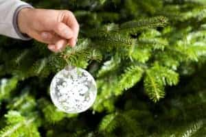 Picture Of Man Hand Decorating Seasonal Risk Christmas Tree