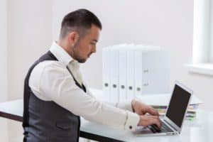 Businessman Using Laptop Workers Comp Policy at Desk