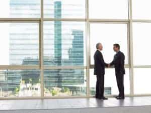 Picture Of Business People Adjusting Services Shaking Hands