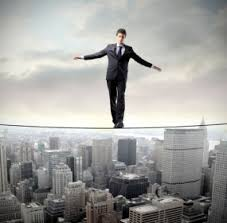 Picture of Man Standing on High Rope Assumption Of Risk Buildings Background
