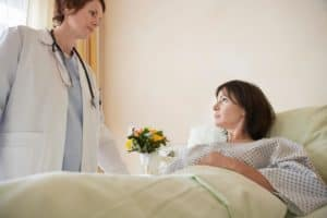 Doctor Talking To Patient Medical Only Claims In Hospital Bed