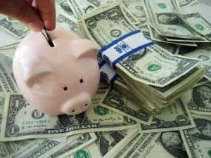 Hands putting coin State Funds on piggy bank with dollars