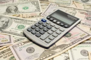 Picture Of Calculator Workers Compensation Program With Money