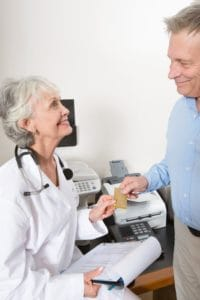 Picture Of Doctor And Senior Man Traditional Workers Comp Holding Gold Card