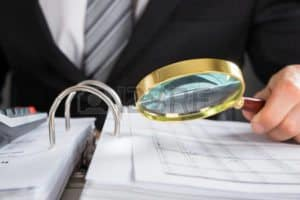 Picture of Workers Holding Magnifying Glass Five Days Notice Premium Audit