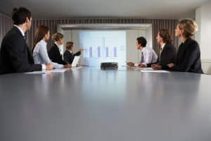 Business People Large Deductible Giving Presentation In Conference Room