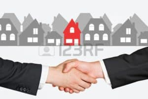 Picture of Hand Shaking Real Deal With Houses At Background
