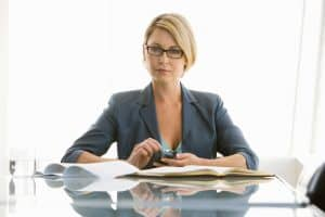 Woman Audit Workpapers On Conference Room Table