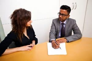 Woman Audit Agreement Talking To Man Signing Papers
