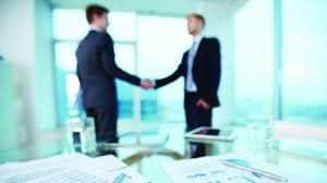 Blurry Picture of Two Man Audit Agreement Shaking Hands