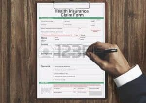 Graphic of form pill up by man hand Medical Fee Schedules Health Insurance Claim Form