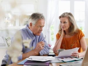 Senior Couple Apologies Looking At Bill Papers