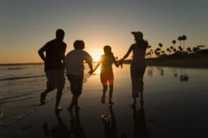 Family Running Workers Comp Through Sea At sunset