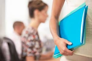 Woman Carrying Folder Payroll Audit vs. Workers Comp Policy Documents