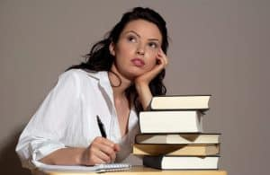 Woman Sitting With Two Books Thinking