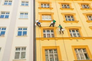 Picture Low Angle View of Window Washers Hanging Construction Dangers Outside