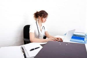 Female Doctor Cutting Workers Comp Costs Using Laptop With Files In Table