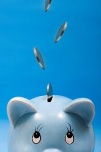Picture Of Coins Dropping Into Piggy Bank Small Deductible Policies In Blue Background