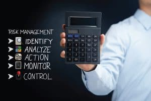 Man Holding Calculator NCPRIMA Presentation Risk Management