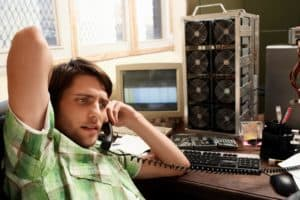 Picture of Man Using Phone Great Reference Tool with Computer Equipment in Background