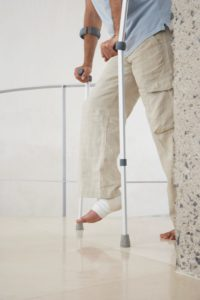 Picture of WC Innovation Injured Man with Wrapped Ankle on Crutches Low Section