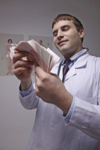 Picture Of Doctor Work Comp Medical Costs Counting Money