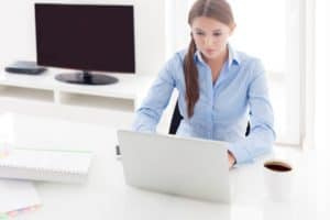 Picture of Businesswoman in Front of A.M. Best TV While Working on Her Laptop