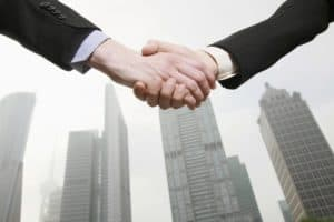 Businessman Hand Shaking Pacific Partnership Agreement Building Background