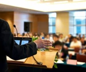 Picture of Man is Making a Speech Work Comp Data Conference Hall