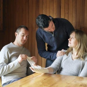 Picture of Man Wrapping Woman Injured Hand Functional Capacity Evaluation While Talking Other Man
